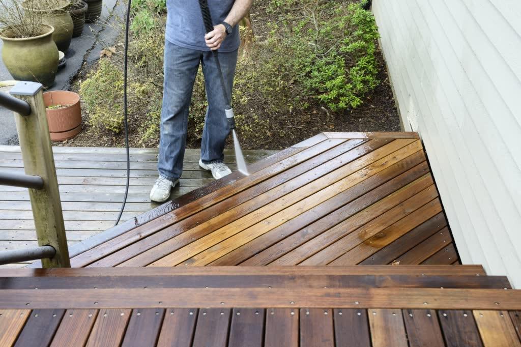 Man power-washing deck